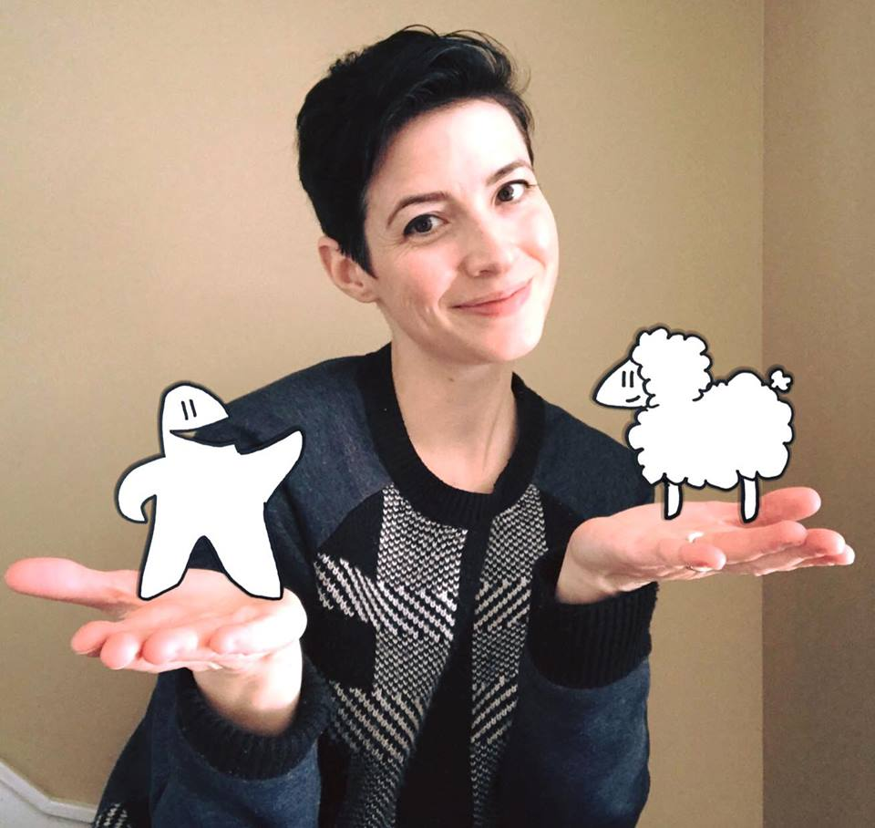Photo of Janelle Tang holding drawings of Meeple and Sheep